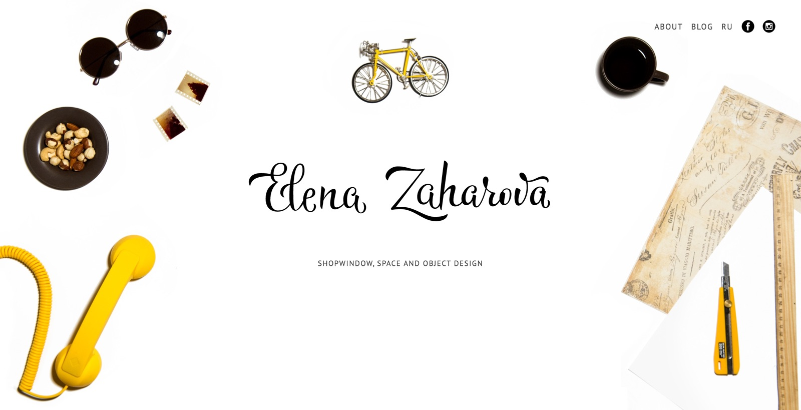 Elena Zaharova's table with sunglasses, toy bicycle, tea cup, photo negatives and sketches